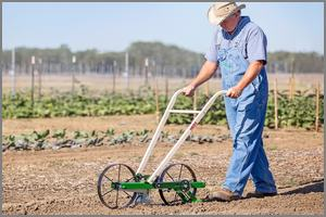 Man pushing a Hoss seeder