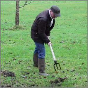 man using a fork hoe to break sod