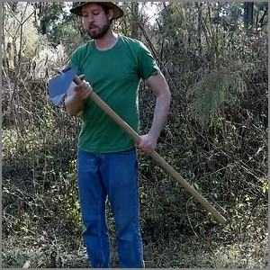 man using a pointed hoe to till soil