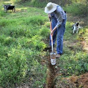 man using a sharpshooter shovel to dig a trench
