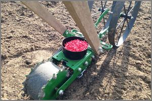 seeder planter in garden, hopper full of seeds