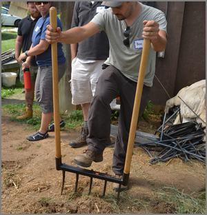 man using broadfork with wood handles
